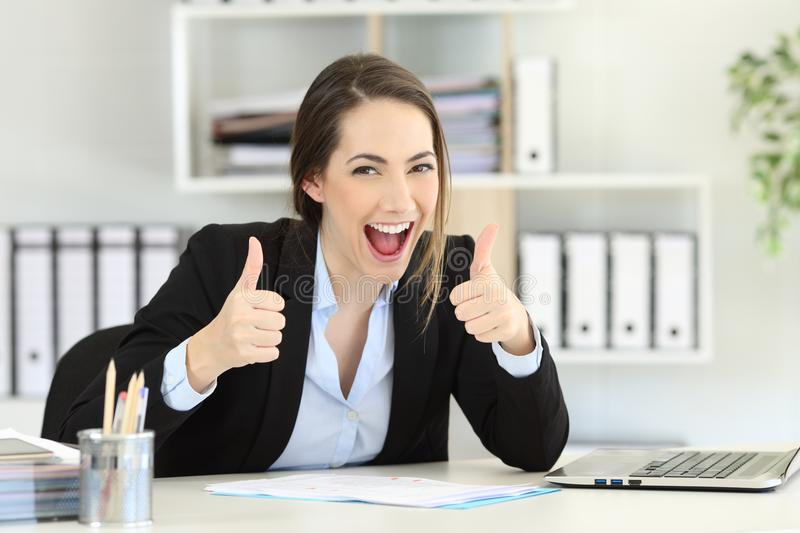 Excited executive looking at camera with thumbs up stock photos