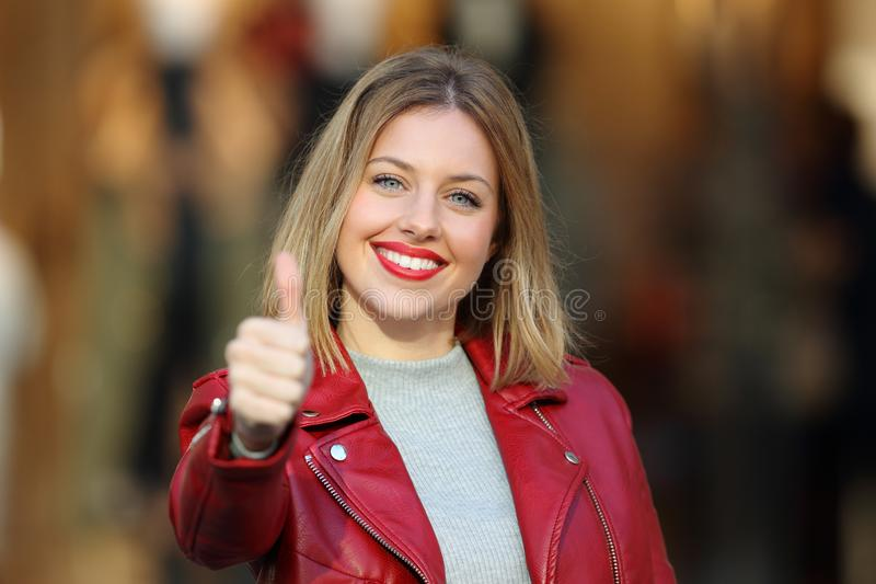Fashion girl with thumb up looking at you stock images