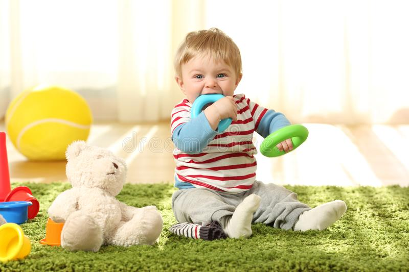 Baby biting toys on a carpet. Front view portrait of a happy baby biting toys on a carpet at home royalty free stock photography
