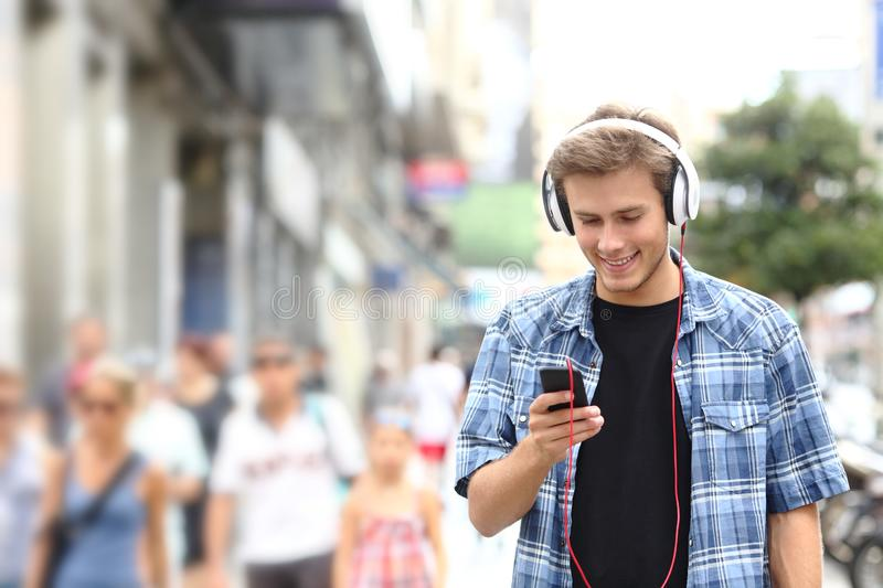 Happy boy walking listening to music in the street stock photography