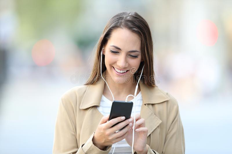 Front view portrait of a happy girl listening to music stock photo