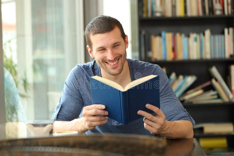 Happy reader reading a paper book in a coffee shop. Front view portrait of a happy reader reading a paper book sitting in a coffee shop stock images