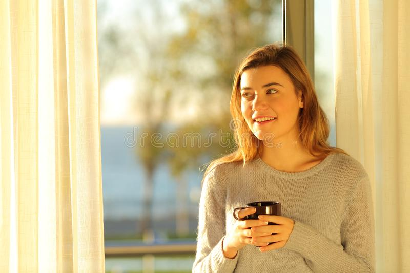 Teen holding mug looking at side at home royalty free stock photography