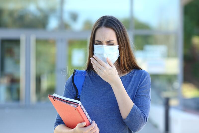 Ill student with a mask coughing in the stret royalty free stock image