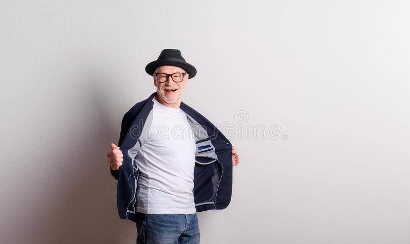 Portrait of a senior man with hat, glasses and jacket in a studio. royalty free stock images