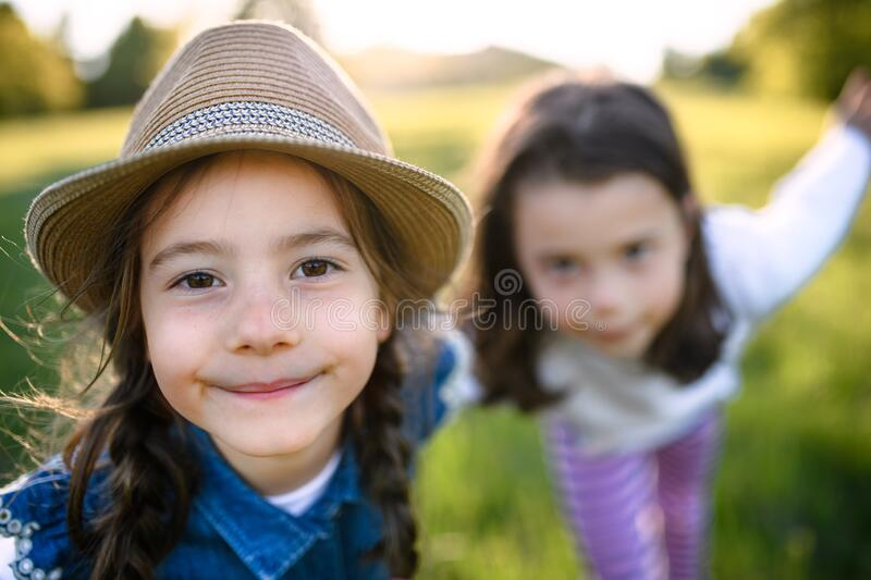 Portrait of two small girls standing outdoors in spring nature, looking at camera. royalty free stock image