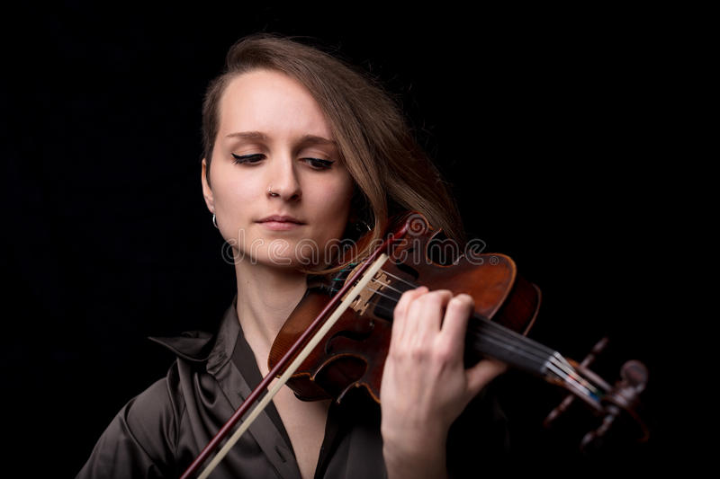Front view portrait of a violinist woman. Portrait of a young beautiful woman violinist player playing her instrument on her shoulder holding bow. portrait in a stock photos