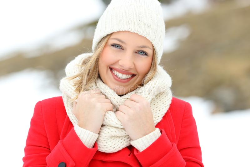 Portrait of a woman in red posing in winter. Front view portrait of a woman in red posing in winter with a snowy mountain in the background stock photo