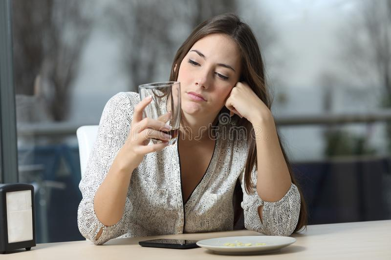 Worried pensive woman looking at glass in a coffee shop stock images