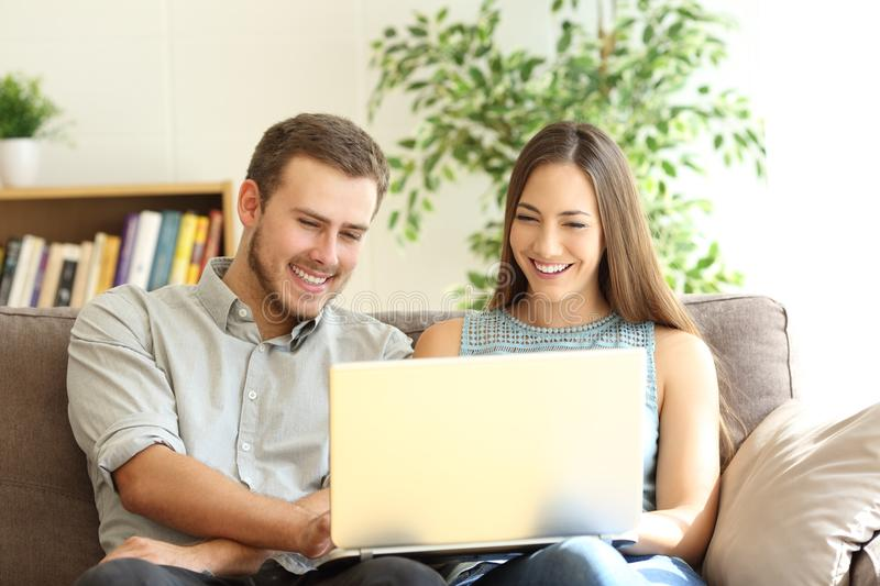 Couple using a laptop together on a couch. Front view portrait of a young happy couple using a laptop together sitting on a sofa in the living room at home royalty free stock photography