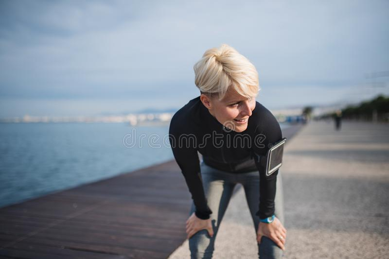 Front view portrait of young sportswoman standing outdoors on beach. stock photography