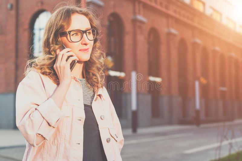 Front view.Portrait of young woman in glasses standing outdoors and talking on cell phone. stock photography