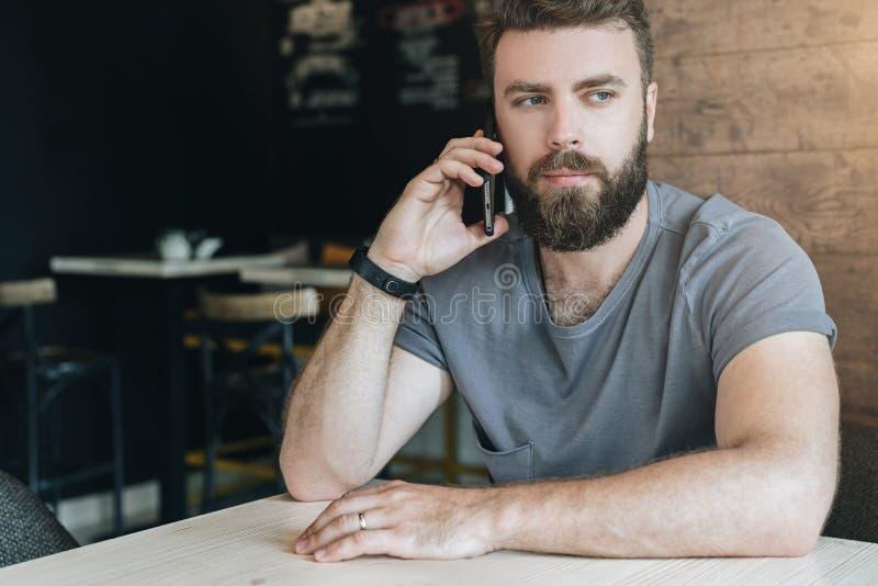 Front View Portret van de jonge knappe gebaarde zitting van de hipstermens in koffie bij lijst en het spreken op zijn celtelefoon stock afbeelding