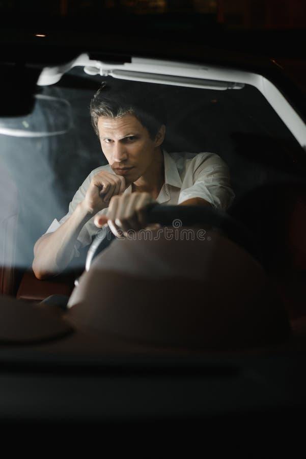 Front View Portret van een knappe mens die zijn auto drijven bij nacht De verkeerslichten achter hem royalty-vrije stock afbeelding