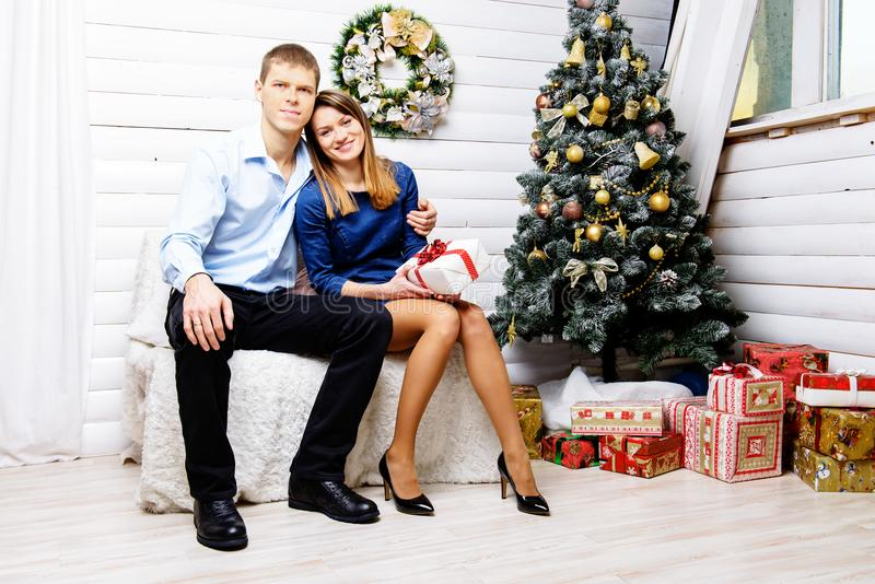 Front view of positive couple in elegant clothes sitting on the stock images