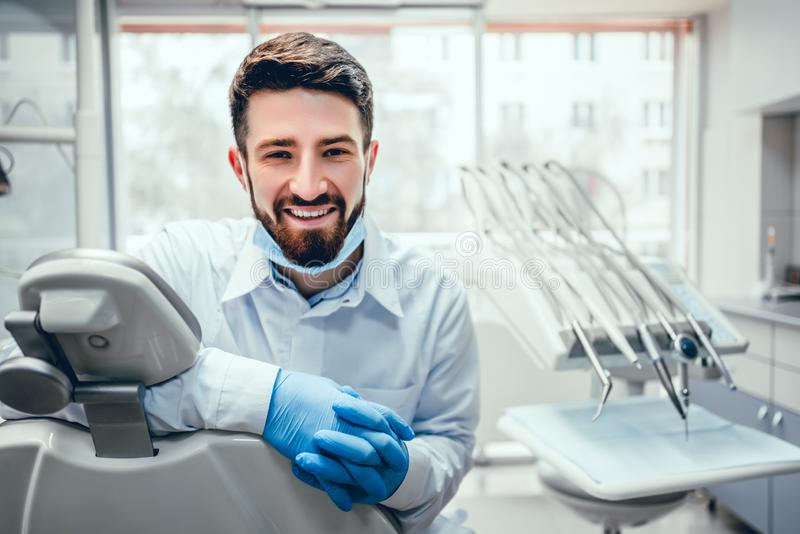 Front view of professional male dentist in white doctor coat and protective gloves sitting in dental chair and equipment, looking stock image