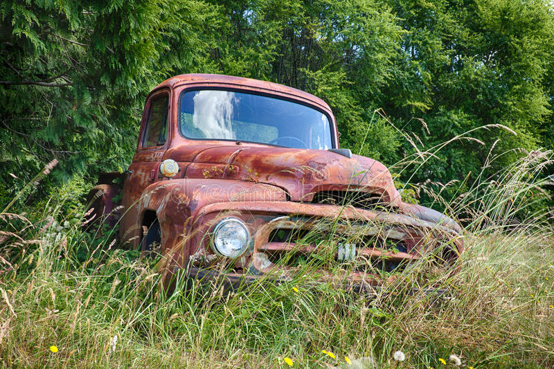 Front View Of Red Truck. WALDRON, USA - JUNE 18, 2015: A frontal view of an old International Harvvester truck that is slowly rusting on a farm on Waldron Island stock photos