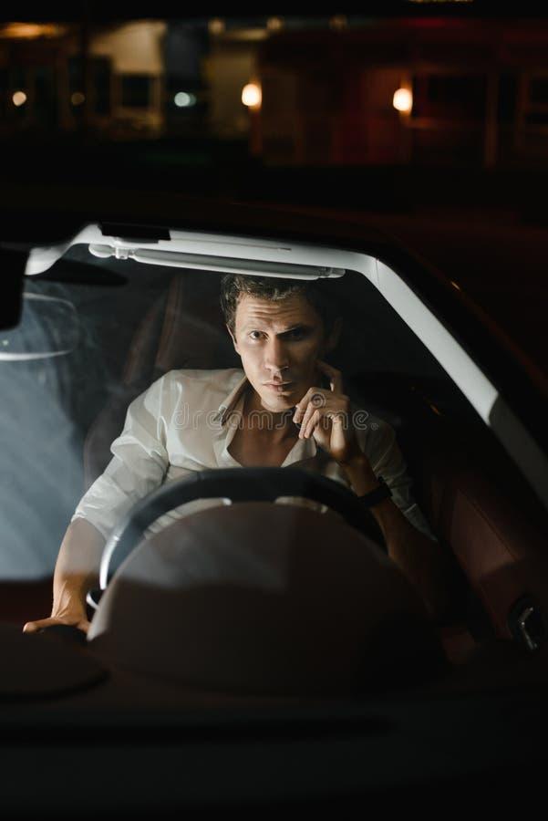 Front View Retrato de um homem considerável que conduz seu carro na noite Os sinais atrás dele foto de stock royalty free