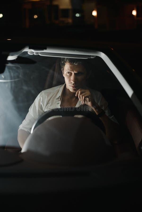 Front View Retrato de un hombre hermoso que conduce su coche en la noche Los semáforos detrás de él imagenes de archivo