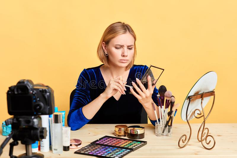 Sad young female makeup artist holds eyeshades palette, dissapointed expression. Front view of sad young female makeup artist holding eyeshades palette stock photography