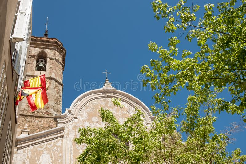 Front view of san marti church in the small catalan town of Sant Celoni on a sunny summer day with trees and spanish flags and. Tower bell stock photos