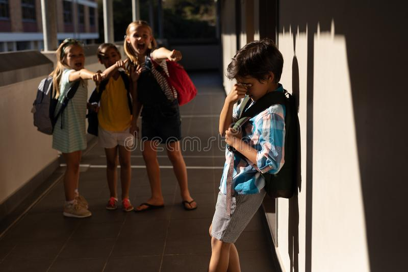 School friends bullying a crying boy in hallway of elementary school stock images