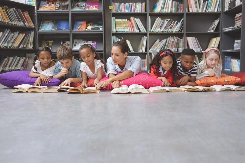 Schoolteacher reading books with his school kids in library. Front view of schoolteacher lying on cushions and reading books with his school kids in library at stock photos