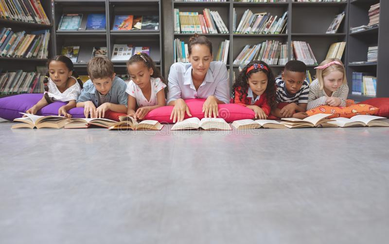 Schoolteacher reading books with his school kids in library. Front view of schoolteacher lying on cushions and reading books with his school kids in library at stock image