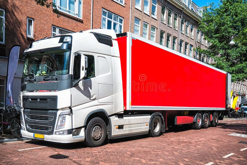 Front View of Semi-Truck with Red Cargo Trailer Driving on the street. Copy space on the trailer royalty free stock photography
