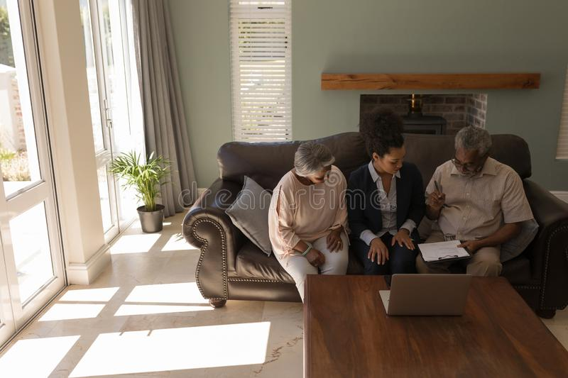 Senior man signing property contract with real estate agent. Front view of a senior African American men signing property contract with real estate agent and royalty free stock images