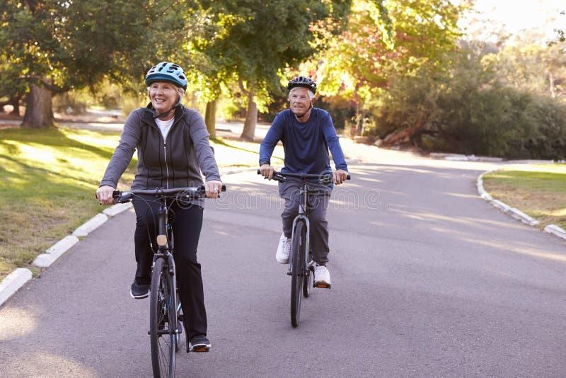Front View Of Senior Couple faisant un cycle par le parc ensemble image stock