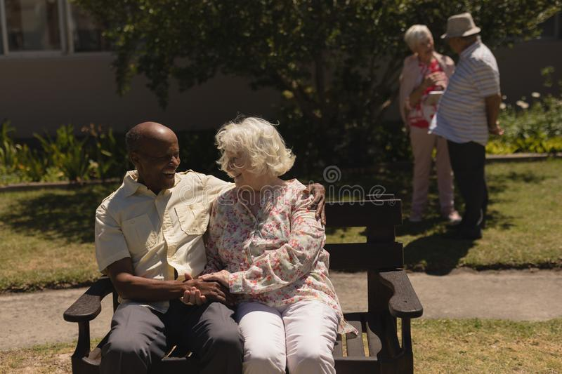Front view of senior couple holding hands and sitting on bench in garden royalty free stock photo