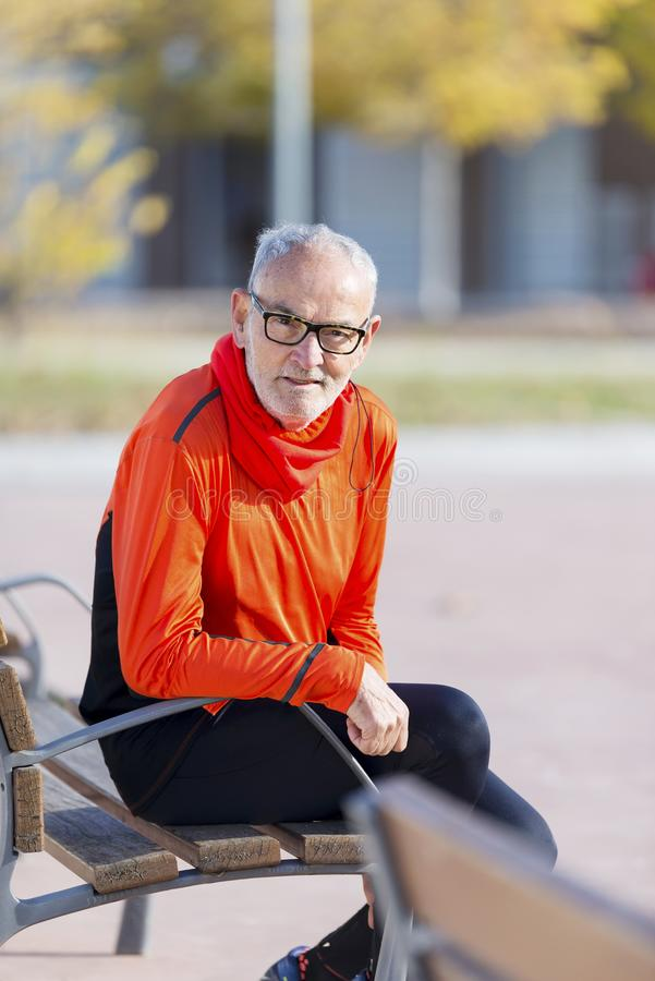 Front view of a senior man in sports clothes sitting in a bench at park while smiling and looking camera in a sunny day stock images