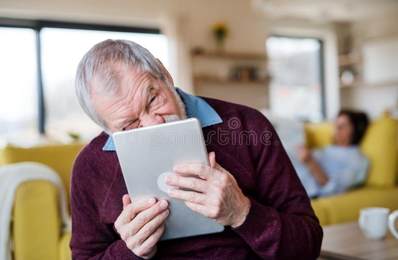 Senior man with tablet indoors at home, making funny faces. Front view of senior men with tablet indoors at home, making funny faces royalty free stock photography