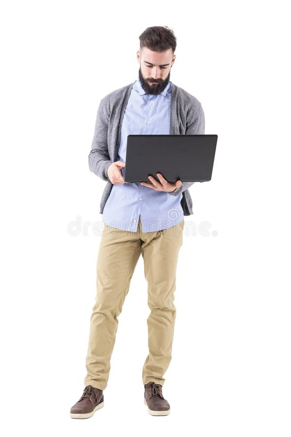 Front view of serious businessman holding and looking at laptop computer. stock photo
