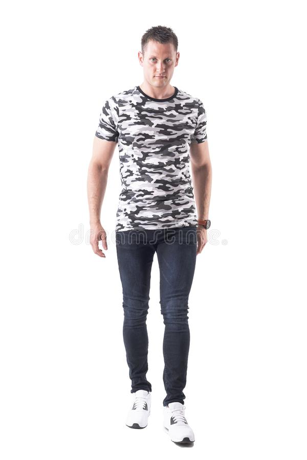 Front view of serious confident man in army shirt walking towards camera with intense look. Full body isolated on white background stock photos