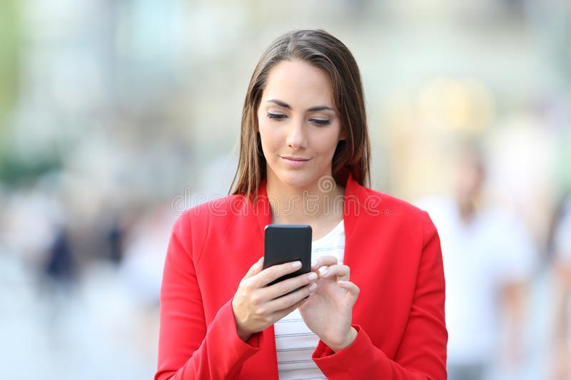 Front view of serious woman in red using phone stock photo