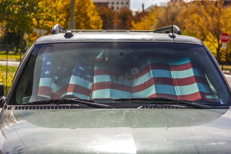 Front view of a shiny gray vehicle against lush trees on a sunny autumn day. Inside the vehicle is a sunshade with an American flag design stock image