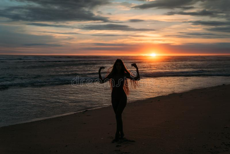 Front view silhouette of attractive woman. Beautiful young girl with long hair walking on the beach, posing at sunset. Concept of travel, relax, yoga stock photo
