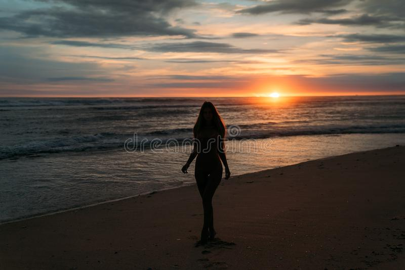 Front view silhouette of attractive woman. Beautiful young girl with long hair walking on the beach, posing at sunset stock photo