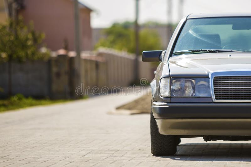 Front view of silver car parked on paved street in quiet area on sunny day at stone fence of residential cottage. Transportation stock images