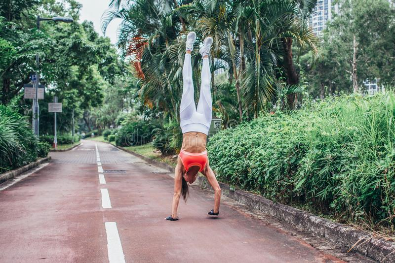 Front view of slim fit young woman practicing yoga doing straight handstand on park path summer day. Sporty girl exercising outdo stock photo
