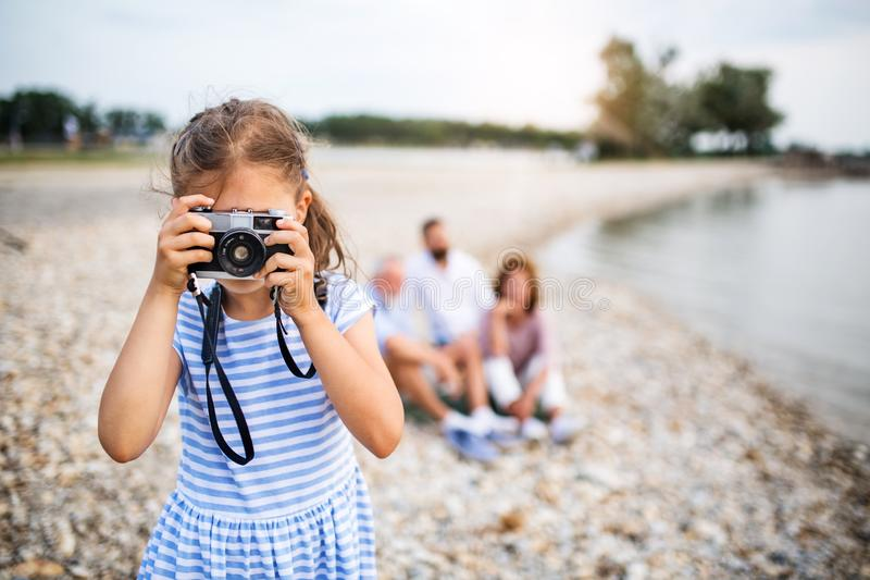 Front view of small girl with camera on a holiday by the lake, taking photos. Front view of small girl with camera on a holiday with family by the lake, taking royalty free stock image