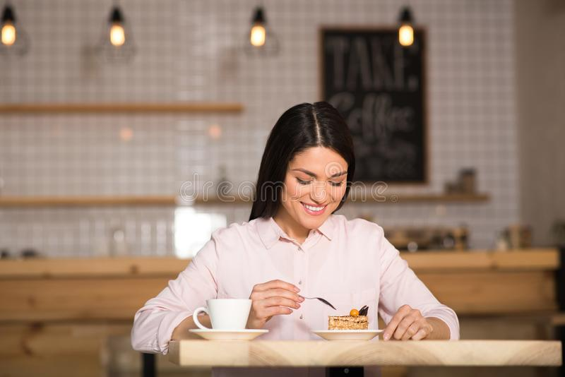 Businesswoman eating cake with coffee. Front view of smiling businesswoman eating cake with coffee in cafe stock image