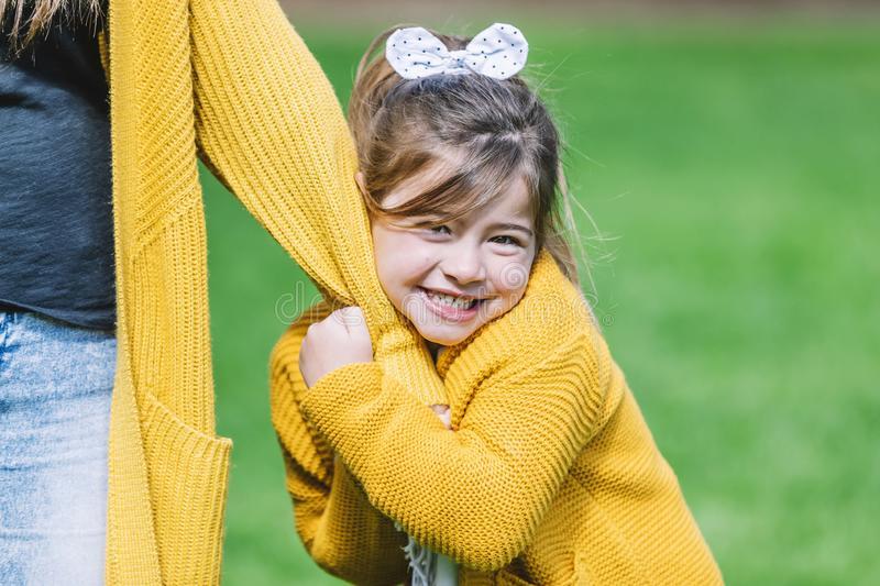 Front view of a smiling little girl with a head tie standing in the park and looking at camera while holding hands with mom in a stock photos