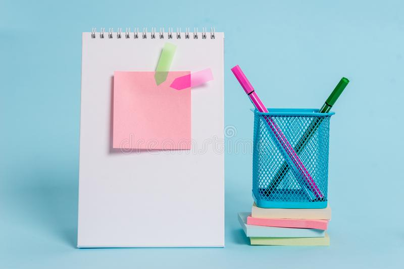 Front view standing spiral blank notebook colored sticky note arrow banners metal pens holder stacked notepads lying stock photo