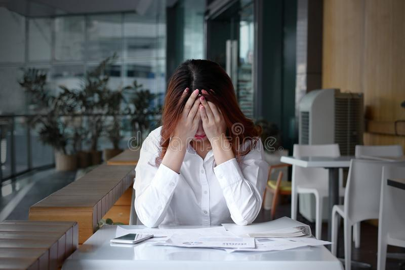 Front view of stressed frustrated young Asian business woman covering face with hands on the desk in office.  stock photo