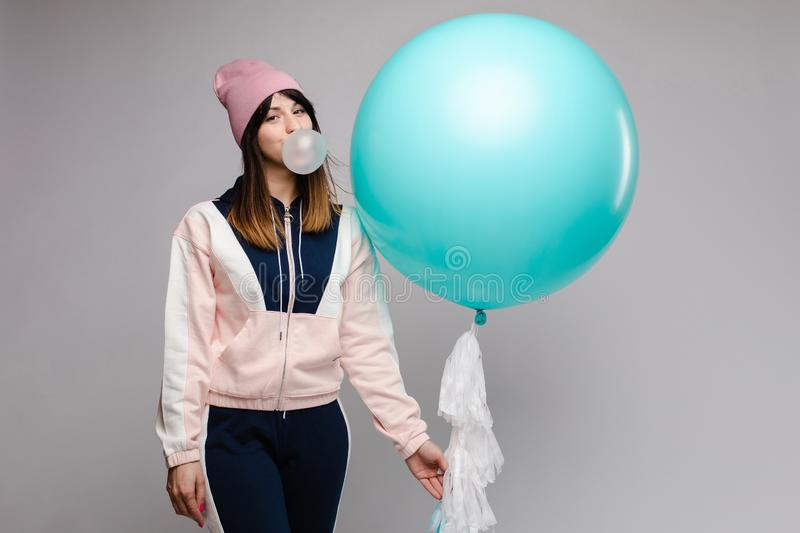 Female teenager chewing gum and keeping big blue balloon. Front view of stylish female teenager wearing tracksuit and hat chewing gum and keeping big blue stock photography