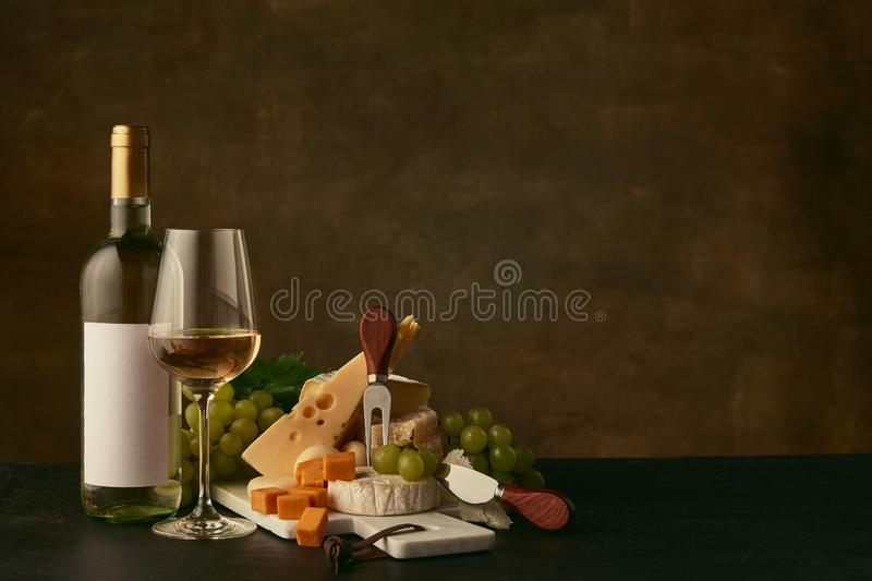 Front view of tasty cheese plate with the wine bottle on dark studio background royalty free stock photography