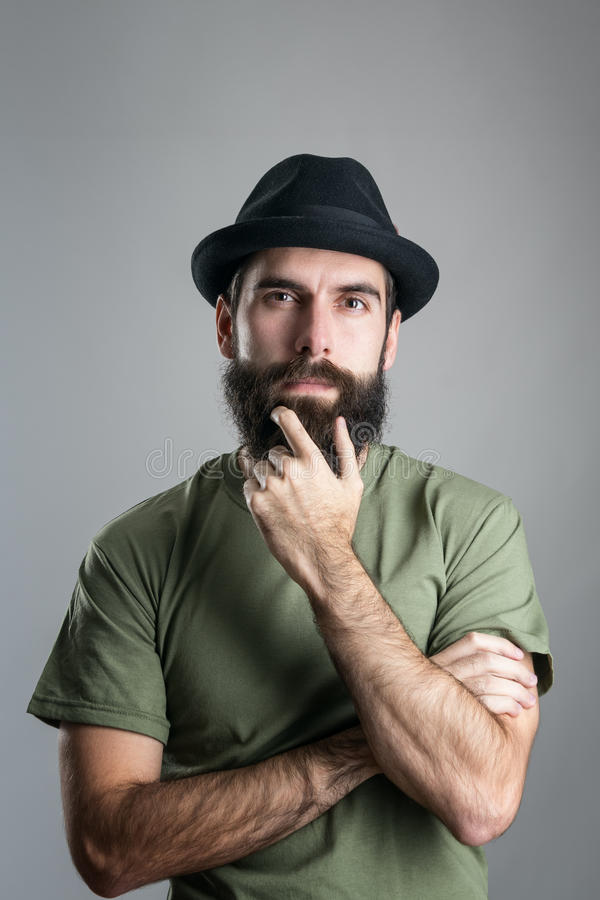 Front view of thoughtful man stroking his beard looking at camera stock photos